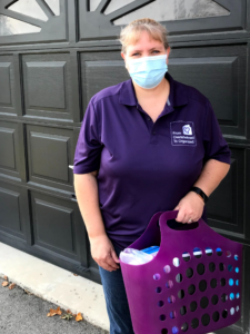 Hilda in a purple shirt with From Overwhelmed To Organized logo, wearing a face mask, and carrying a purple basket with organizing and sanitizing supplies