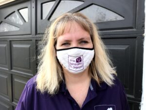 Hilda wearing a white mask with the purple From Overwhelmed To Organized logo on it