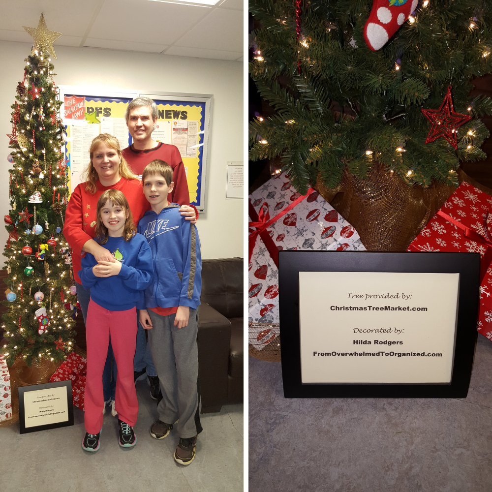 A family beside a decorated Christmas tree and a sign saying the tree was donated by ChristmasTreeMarket.com and decorated by Hilda Rodgers of From Overwhelmed To Organized