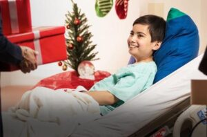 Boy in the hospital at Christmas being given a gift