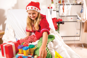 Girl in hospital at Christmas opening a stocking