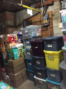 An organized storage room with stacks of bins and boxes, labeled with their contents