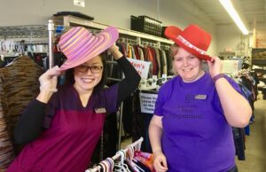 Two professional organizers helping organize clothing and accessories at a group volunteer day